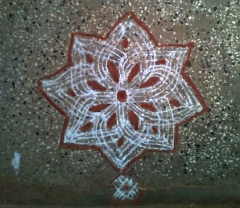Traditional Kolam made with lines and filled with red stone color